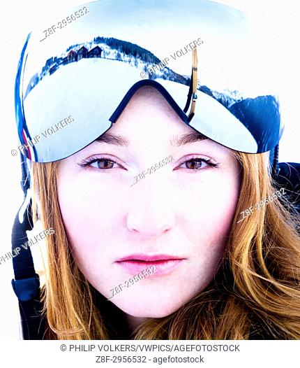 Ginger young woman wearing ski glasses in the Alps