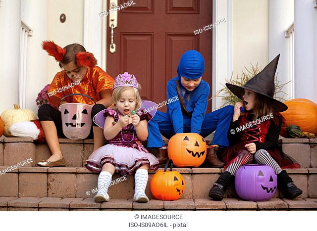 Children enjoying treats on steps