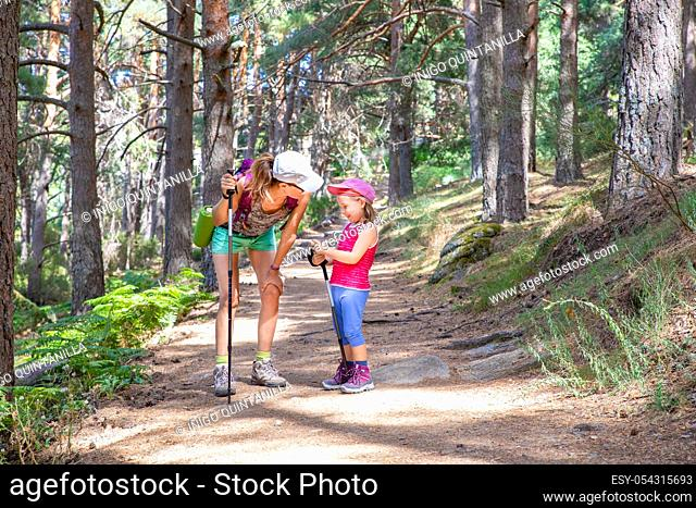 mountaineer family laughing (woman and five years old girl), with caps and trekking sticks, on a footpath in a forest of Canencia (Madrid, Spain, Europe)