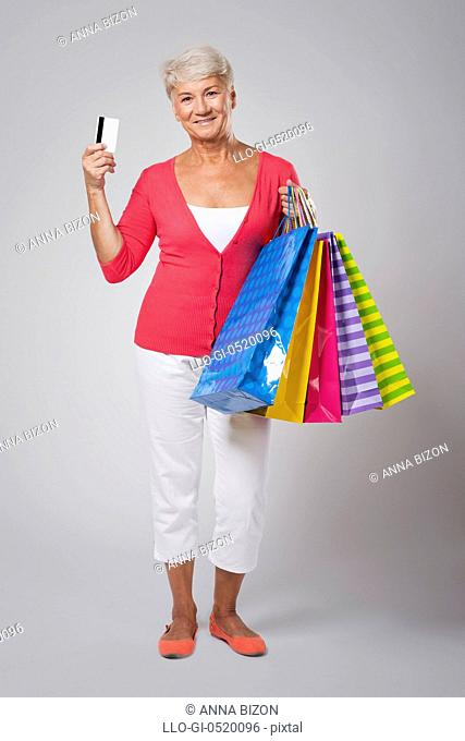 Beautiful senior woman with shopping bags and credit card. Debica, Poland