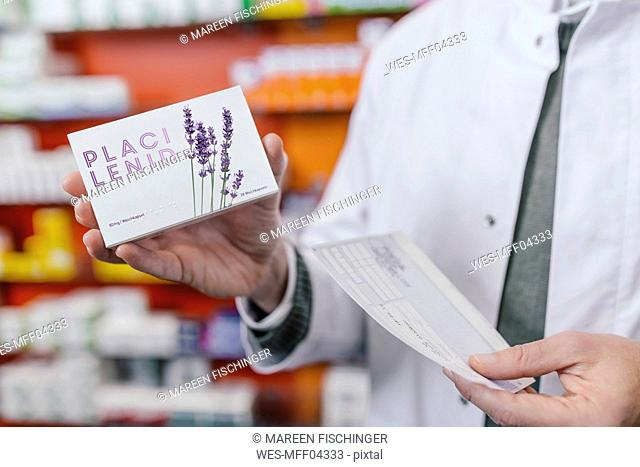 Pharmacist holding tablet package and prescription in pharmacy