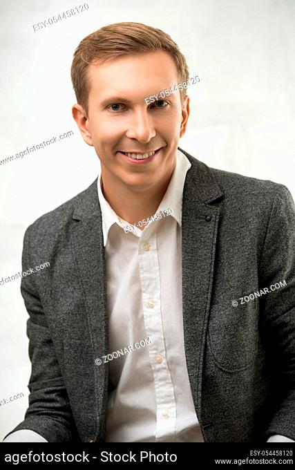 Young fair handsome man wearing white shirt, jacket and jeans with a happy smile portrait against white wall
