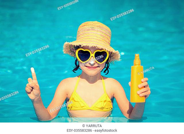 Funny portrait of child. Kid having fun in swimming pool outdoors. Summer vacation and healthy lifestyle concept