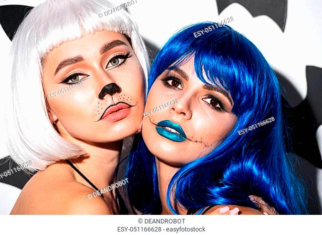Image of two serious young women in halloween costumes on party over white background. Looking camera