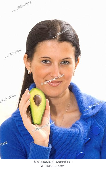 Beautiful young woman holding a halved avocado fruit