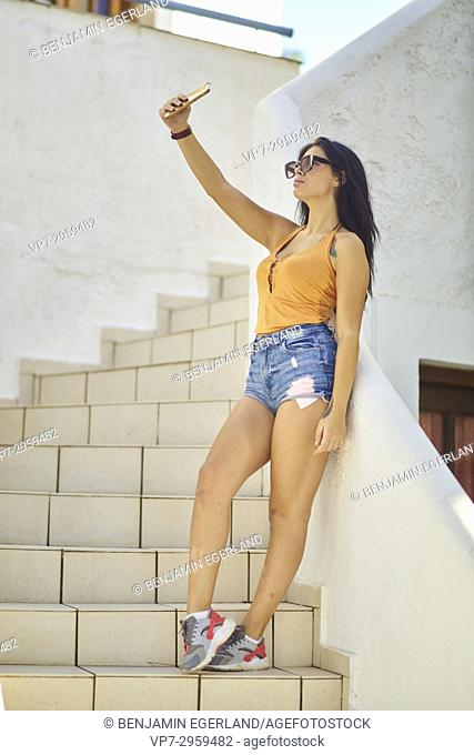 young woman taking a selfie while standing on stairs. 20 years old. Greek ethnicity. In Hersonissos, Crete, Greece