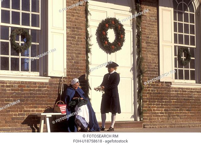 Colonial Williamsburg, Virginia, VA, Williamsburg, Interpreters dressed in colonial costumes talk outside the Courthouse which is decorated with a Christmas...