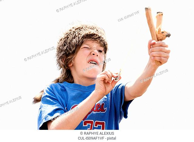 Boy wearing trapper's hat playing with sling shot
