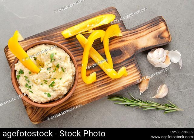 Flat lay view at vegetable Hummus dip dish topped with olive oil served with yellow sweet bell pepper slices