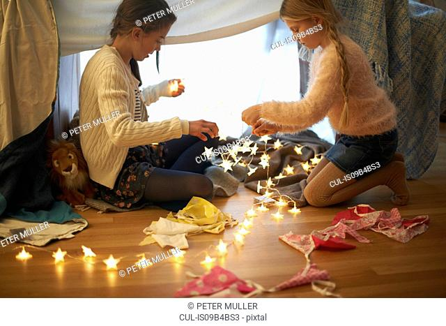 Two sisters in bedroom den preparing star shape lights