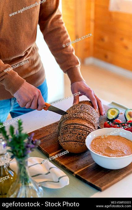 Close-up of man cutting bread in a wooden cabin