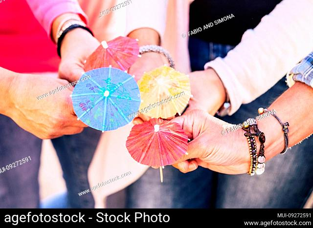 Closeup with group of people holding and showing four cocktail umbrellas together - friendship and team cooperation celebrating concept lifestyle