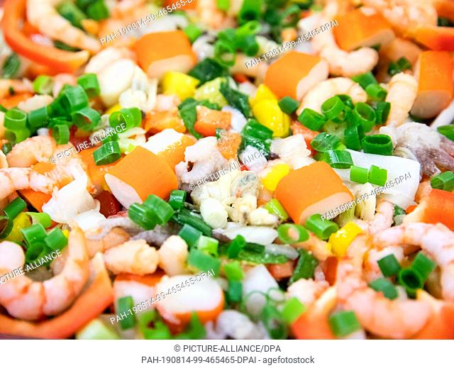 14 August 2019, Hamburg: Seafood salad lie in a bowl with a wholesaler in the fish market Hamburg Altona. Photo: Christian Charisius/dpa