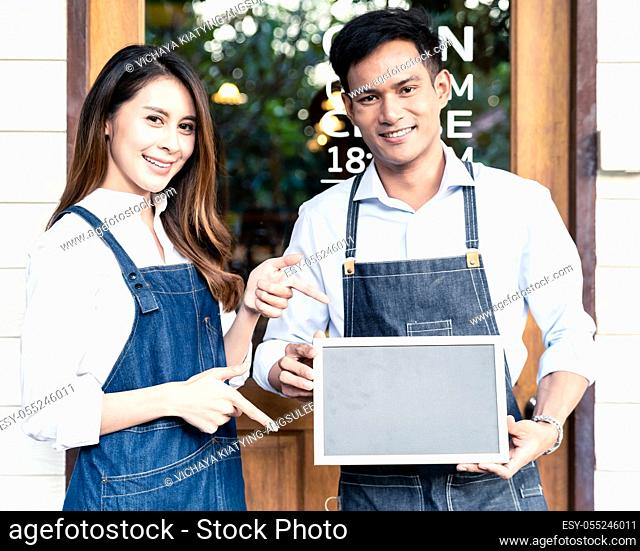 Asian young adult owners of Small business cafe holding blank chalkboard in front of coffee retail shop. Using as startup SME concept. Square crop