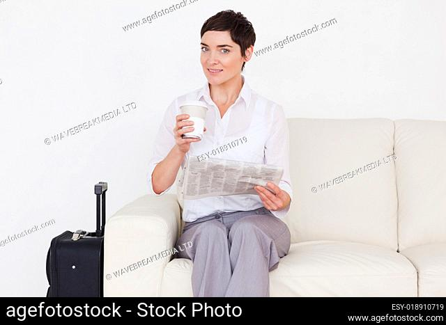 Happy brunette woman with a suitcase, a newspaper and a cup