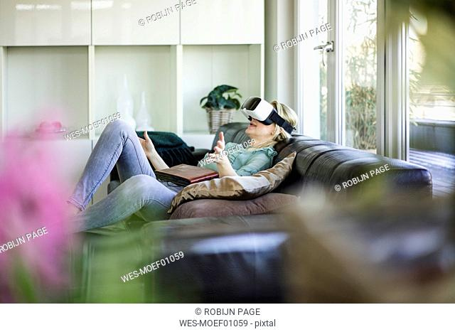 Woman lying on the couch with photo album using Virtual Reality Glasses