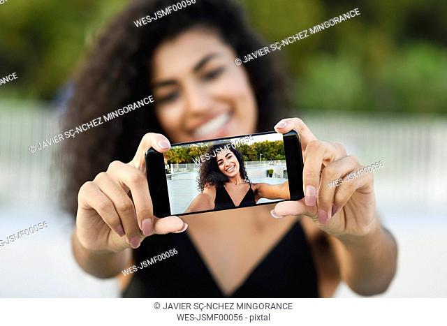 Happy young woman taking selfie with cell phone, close-up