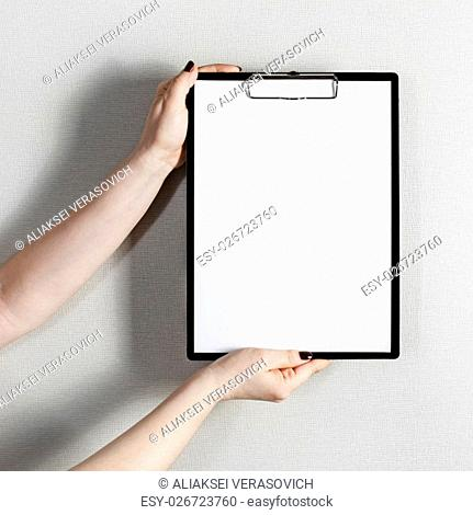 Blank paper poster in female hands. Clipboard with a blank paper. Mock-up for graphic designers portfolios