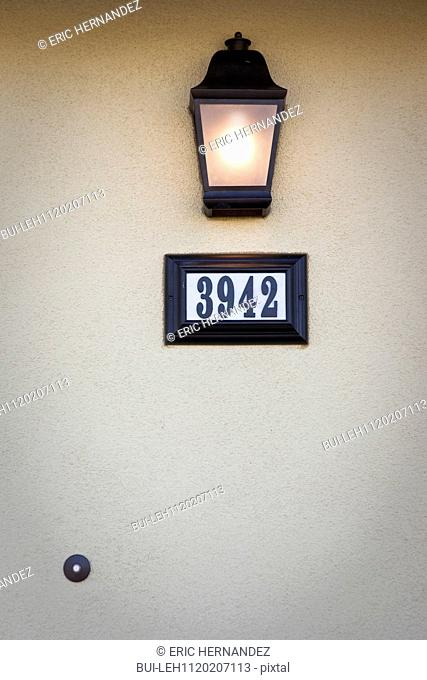 Detail shot of a wall lantern and door number at Ontario; California; USA