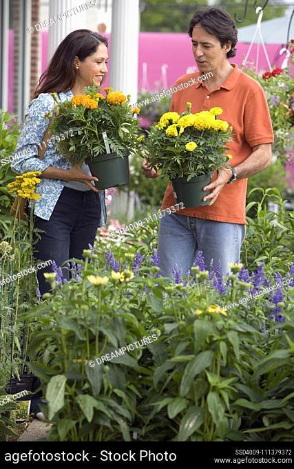 Hispanic couple holding potted plants at nursery