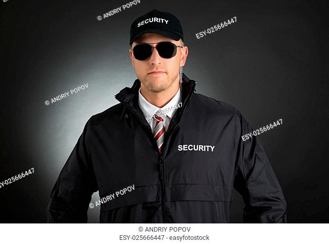 Portrait Of Young Bodyguard In Uniform Wearing Sunglasses Over Black Background