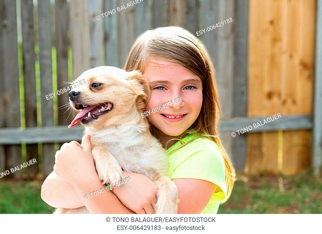 Blond kid girl with chihuahua pet dog playing happy outdoor