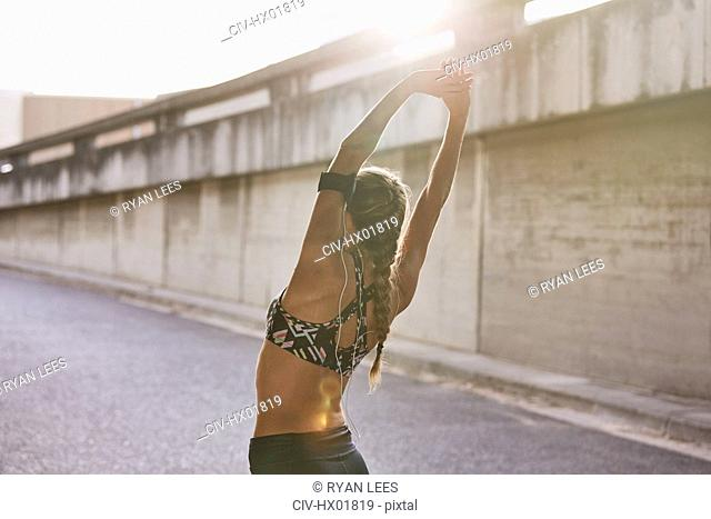 Fit female runner in sports bra stretching arms overhead on urban street
