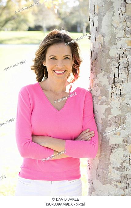 Portrait of mature woman leaning against tree in park