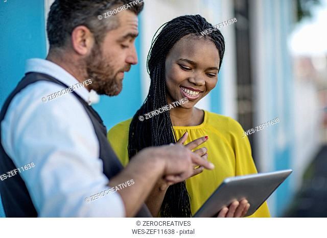 Man and smiling woman looking at tablet together