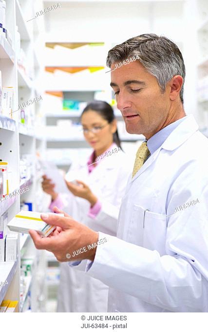 Pharmacists reading pack of medicine from pharmacy shelf