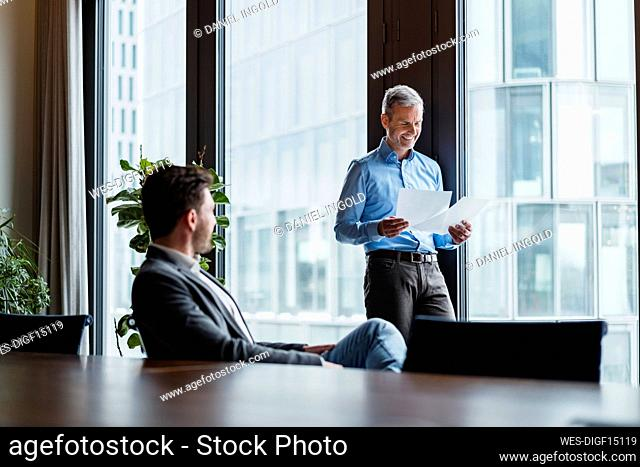 Smiling male entrepreneur examining papers while working with colleague at work place