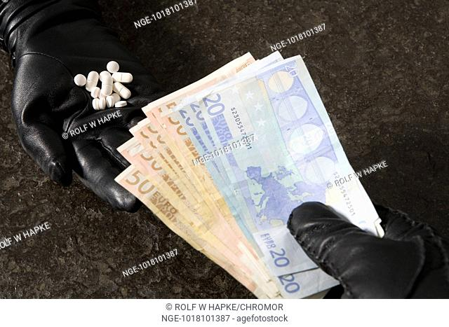 2 hands in black leather gloves exchanging pills for money