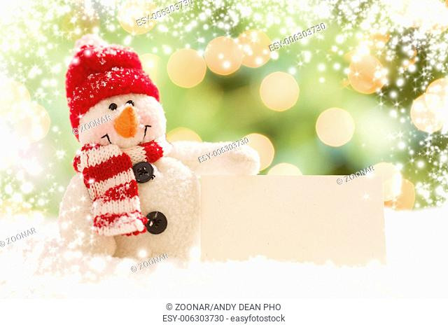 Snowman with Blank White Card Over Abstract Snow and LIght