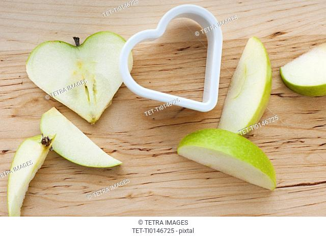 Heart shaped apples with cutter on chopping board