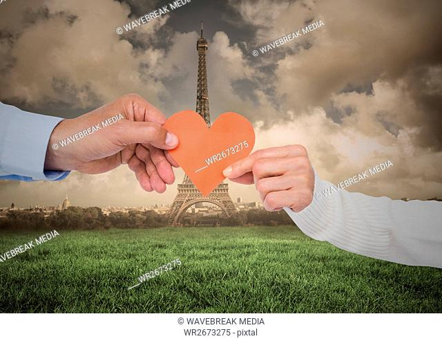 Couples hand holding heart against digitally generated eiffel tower at distance