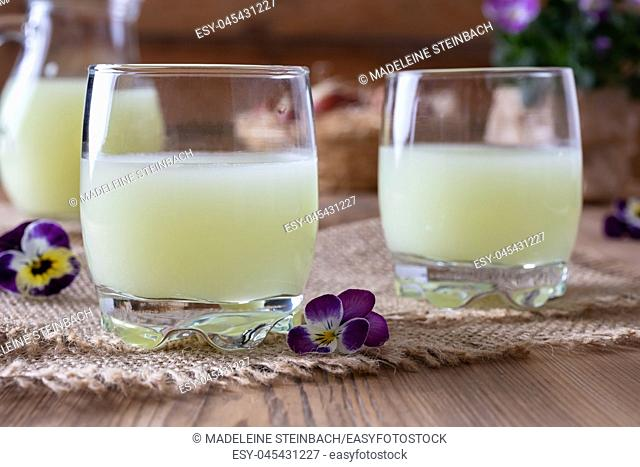 Two glasses of fresh whey with pansy flowers