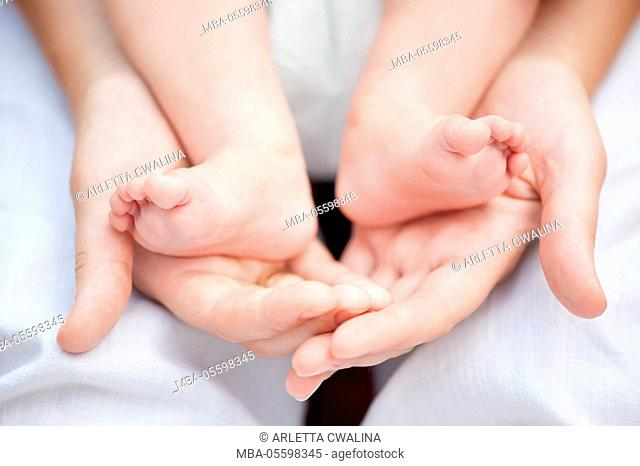Gentle mother hands hugging feet of her child, parent love, MR available on request