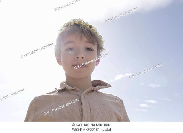 Portrait of boy wearing flowers at backlight