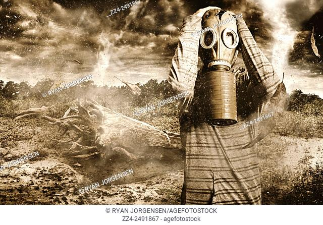 Creative portrait of a weary man standing in a baron wasteland wearing war torn gasmask looking to the skies of terror and toxic vapour. The Downfall