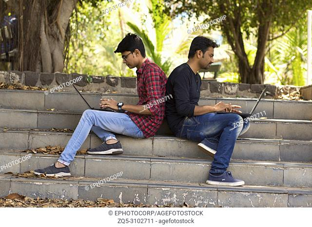 Young students using laptop lean on each other back to back on strairs in park