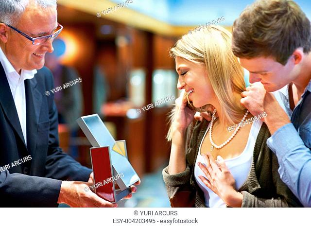 Mature jeweller standing with a young couple trying on a pearl necklace