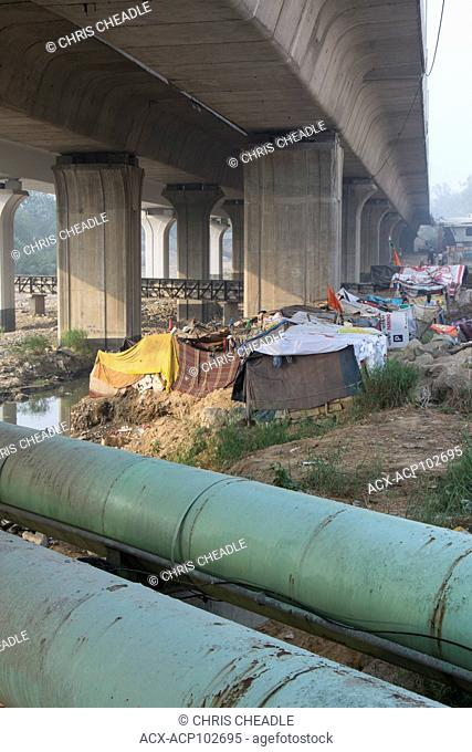 Makeshift shanty housing under freeway, Delhi, India