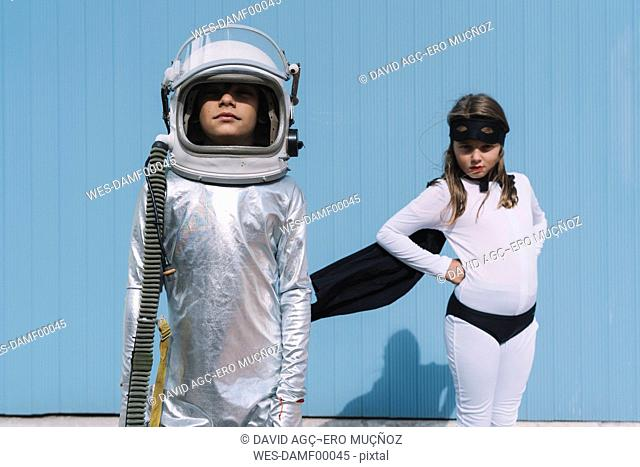 Two kids in astronaut and superhero costumes