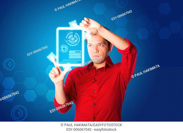 Business man in red shirt looking at digital graph chart on hologram touch screen computer tablet device, on blue
