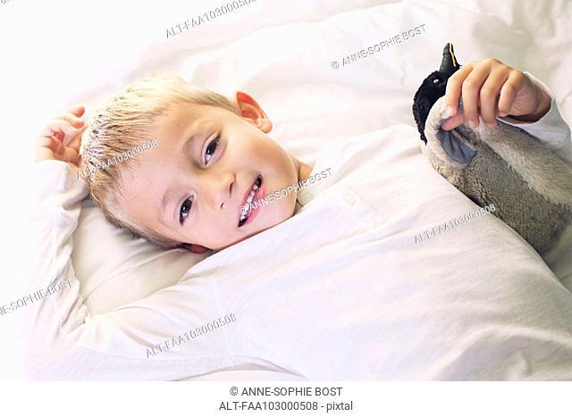 Boy lying down with stuffed penguin, portrait