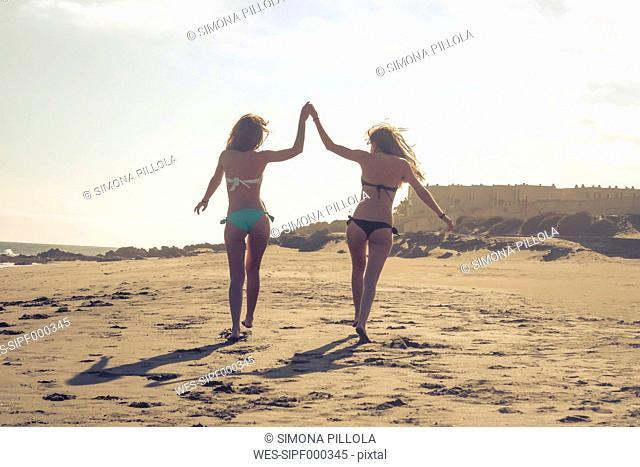 Spain, Tenerife, two female friends walking on the beach