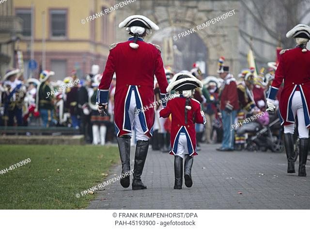 A small and a tall carnival reveller walk through the city in Mainz, Germany, 01 January 2014. The parade of the Mainzer Garden(lit