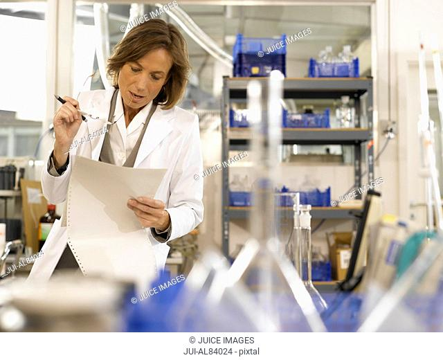 Senior female scientist reading paperwork in laboratory
