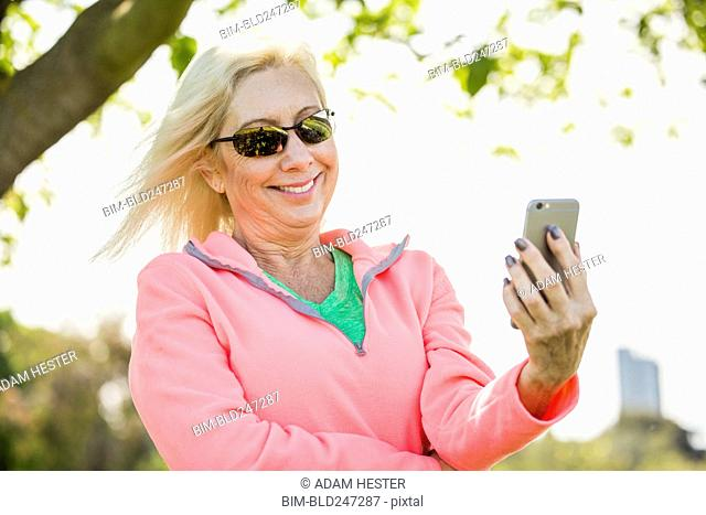 Wind blowing hair of Caucasian woman texting on cell phone