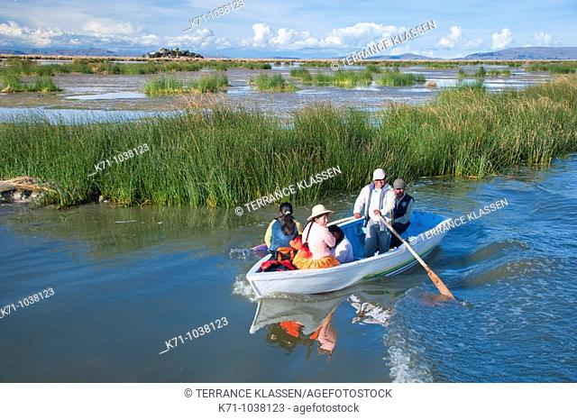 A family on a boat near the floating Islands in Lake Titicaca, Peru, South America